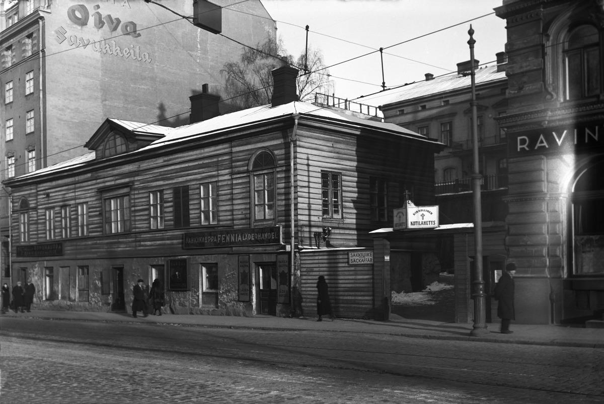 Unioninkatu 43. Etualalla kadun varrella kaksikerroksinen puinen rakennus, joka purettiin tontilta 1940 -luvulle tultaessa