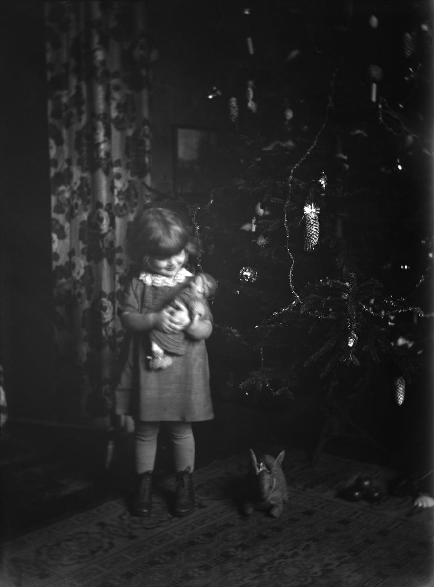 Pieni tyttö joulukuusen vieressä nukke sylissään.