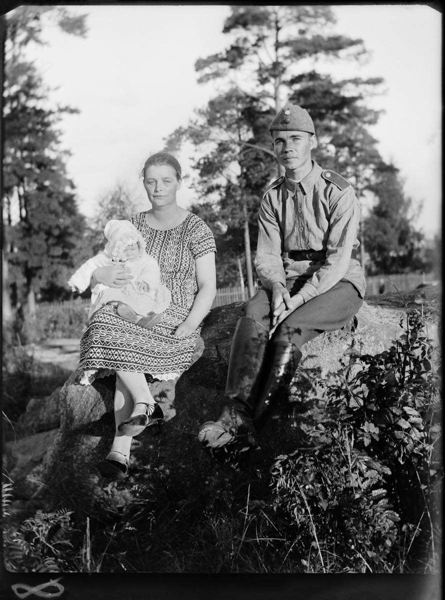 Kolme henkilöä istumassa kivenlohkareilla
