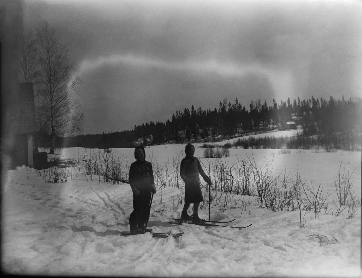 Kaksi lasta hiihtämässä lumisessa maisemassa.