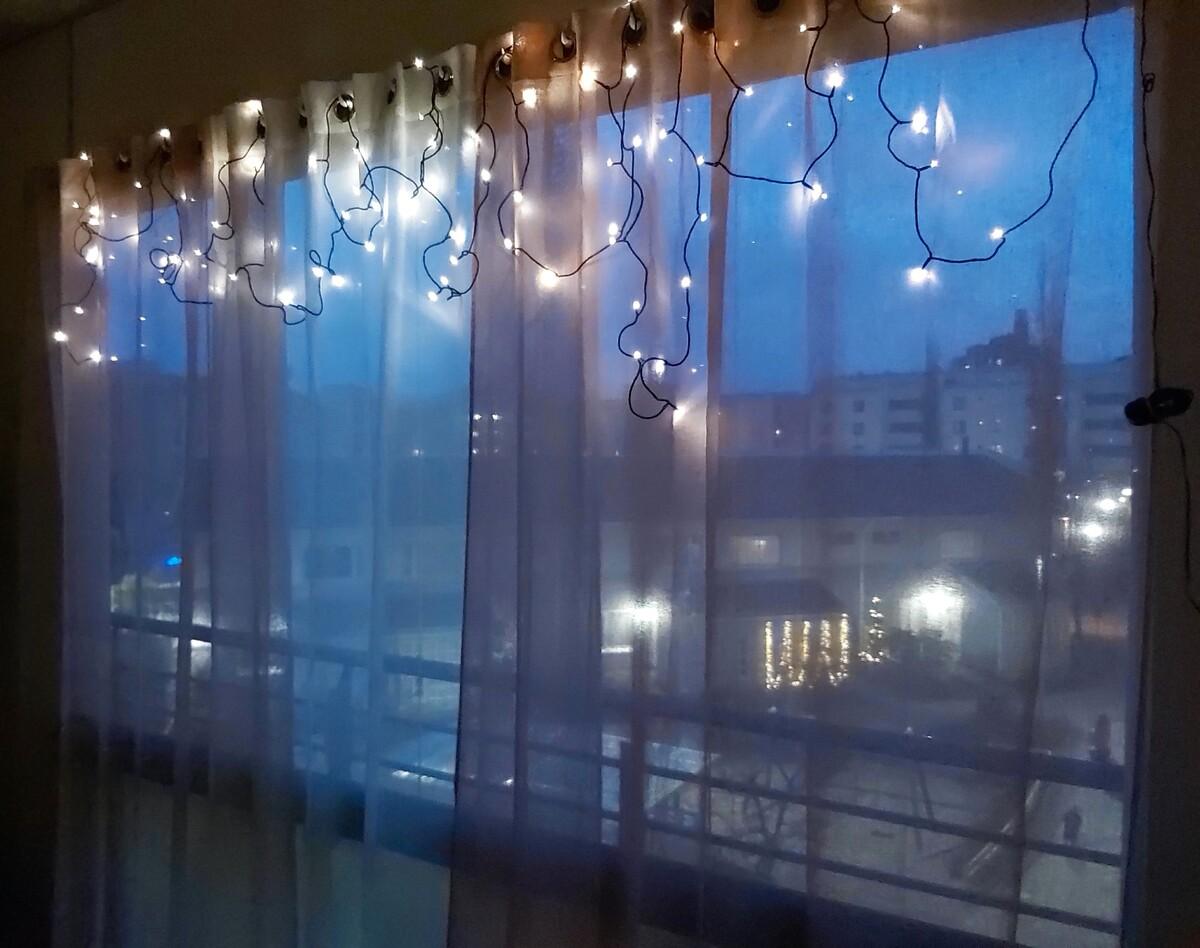 Näkymä asuinkerrostalon pihalle jouluvaloin yläosastaan koristellun ikkunan ja ikkunaverhon läpi Herttoniemenrannassa