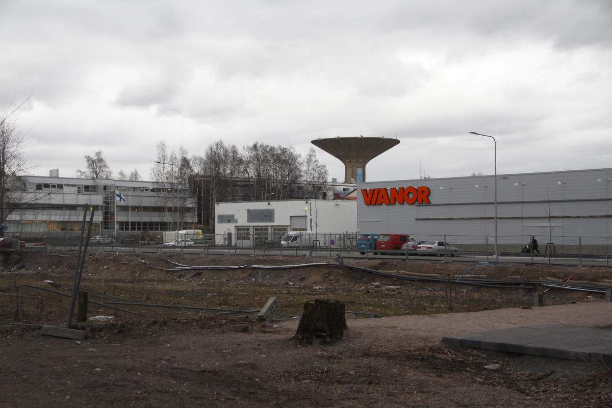Tyhjä, rakentamaton tontti Herttoniemen teollisuusalueella, Kirvesmiehenkatu 4. Kadun toisella puolella Kirvesmiehenkatu 5, 7. Vasemmalla Marimekon pääkonttori Puusepänkatu 4. Taustalla Roihuvuoren vesitorni.