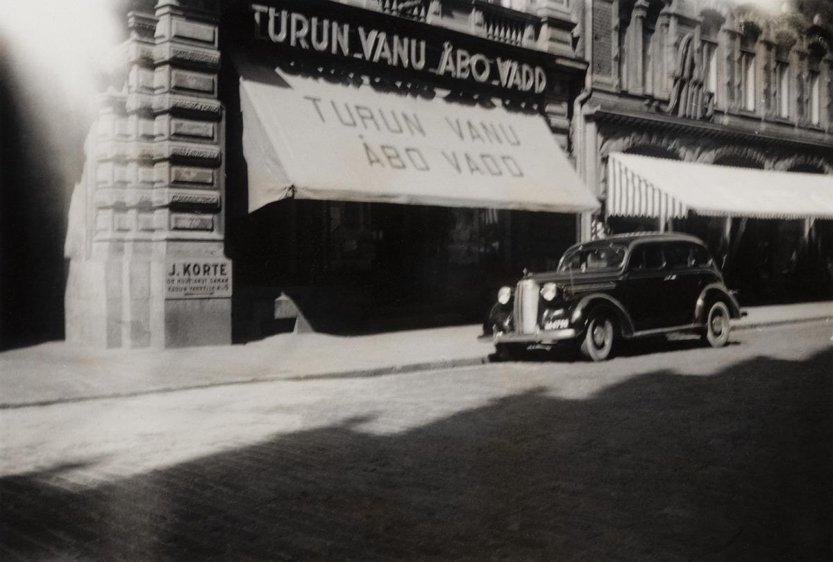 Turun Vanun (alkuaan Turun Vanuliike) uusi, lokakuussa 1937 perustettu myymälä, Kluuvikatu 2. Talon eteen on pysäköity musta henkilöauto, mutta muuten katu on tyhjä