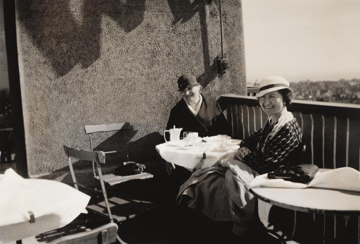 Edla Alander ja hänen miniänsä Anna Alander kahvilla Hotelli Tornin kattoterassilla, Yrjönkatu 26. Kalevankatu 5. Kuva on otettu etelän suuntaan, taustalla näkyy Metodistikirkon torni Fredrikintorin laidalta.