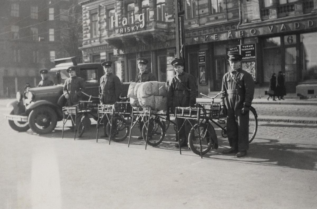 Turun Vanuliikkeen (myöhemmin Turun Vanu) polkupyörä- ja autolähettejä univormuissaan myymälän edessä, Länsi-Heikinkatu 6 (nykyään Mannerheimintie 2a)