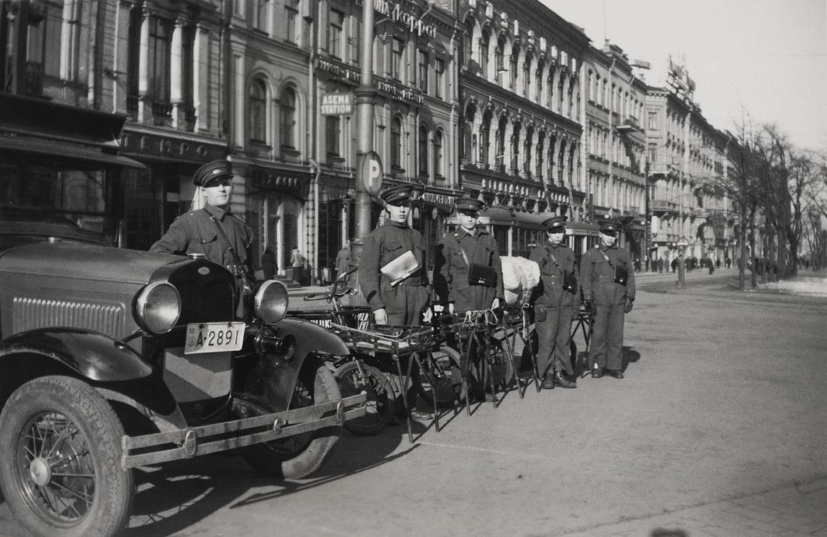 Turun Vanuliikkeen (myöhemmin Turun Vanu) autonkuljettaja ja neljä nuorta polkupyörillä liikkuvaa lähettipoikaa univormuissaan