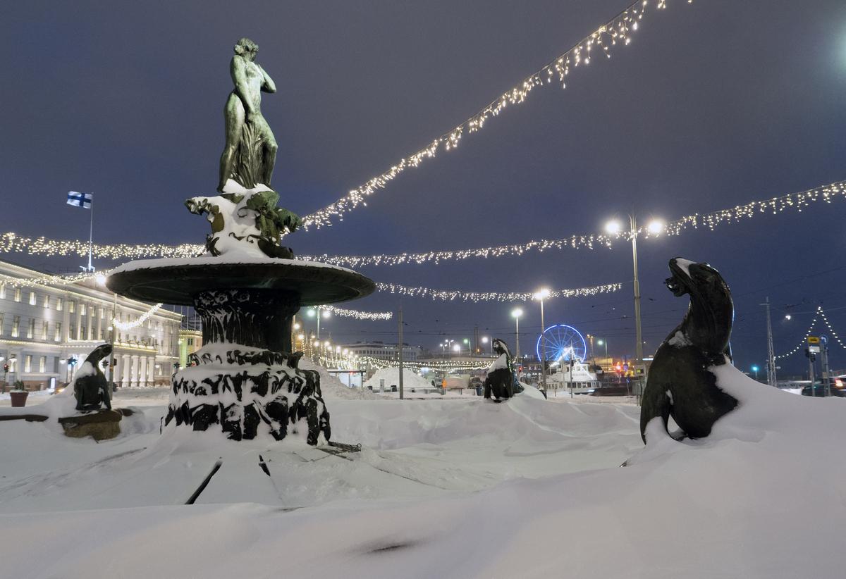 Jouluvalojen ympäröimä, osittain lumen peittämä Havis Amanda -veistos Kauppatorilla runsaslumisena talvena