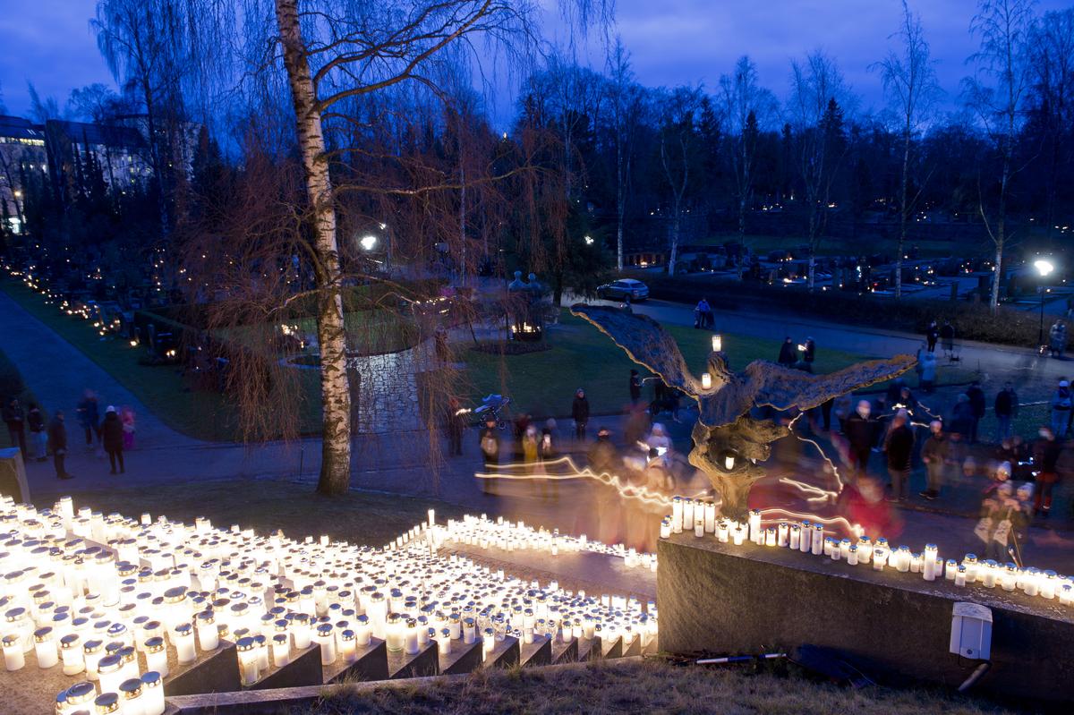 Hautakynttilöitä Hietaniemen hautausmaalla jouluaatton iltapäivän sinisenä hetkenä