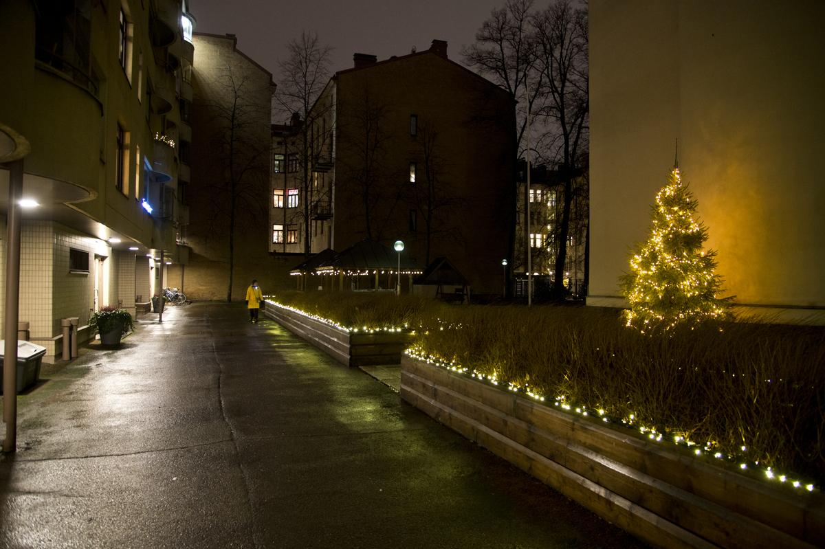 Jouluvaloja asuintalojen sisäpihalla, Uudenmaankatu 19-21. Pihalla olevien istutusalueiden reunoihin ja pihalla olevaan joulukuuseen on laitettu jouluvaloketjuja