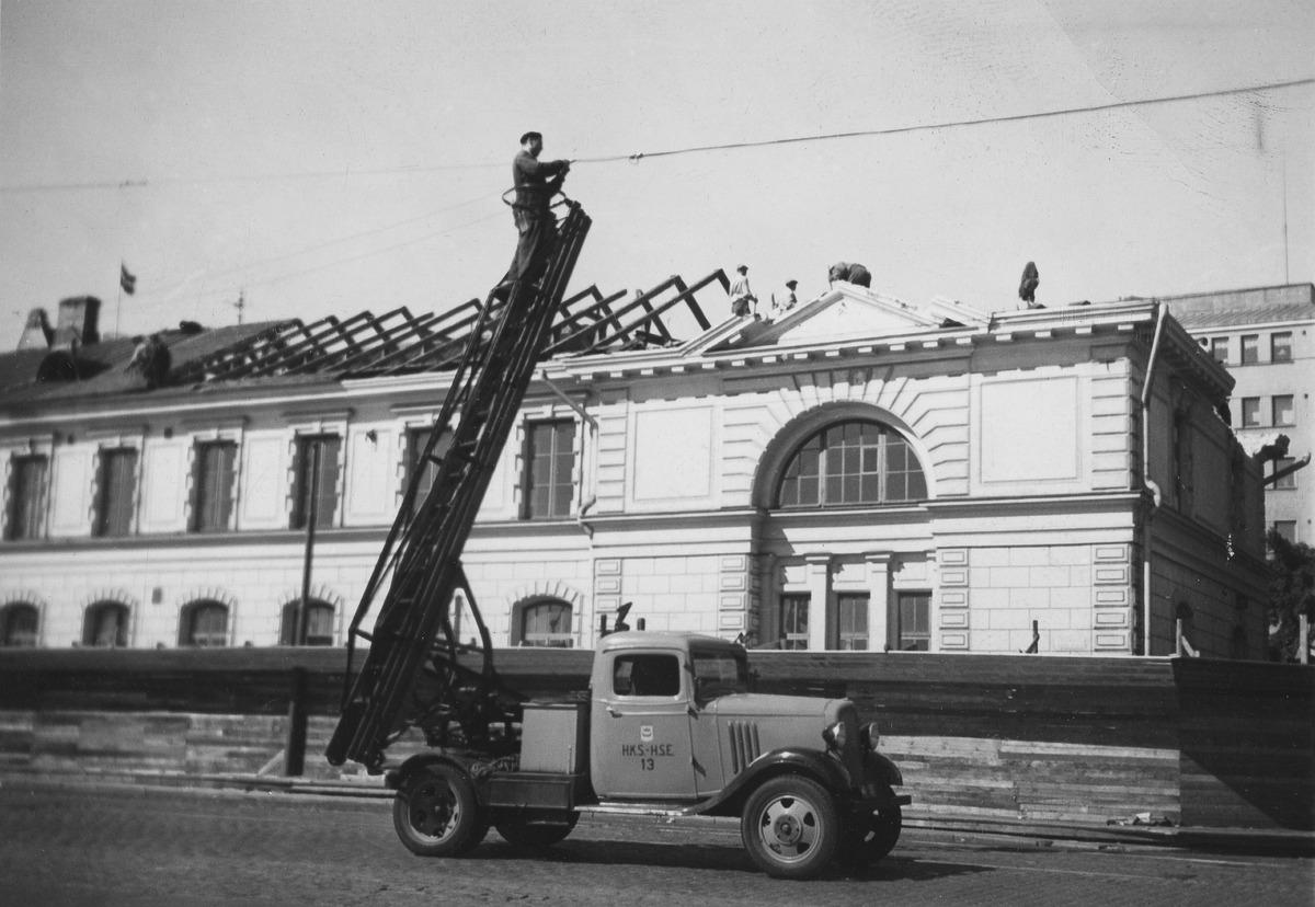 Helsingin kaupungin sähkölaitoksen työntekijä vaihtamassa lamppua Eteläranta 10 kohdalla
